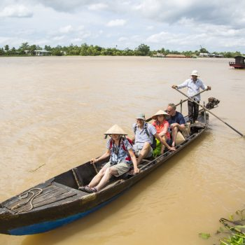Happy tourists relaxing on a Mekong delta river tour