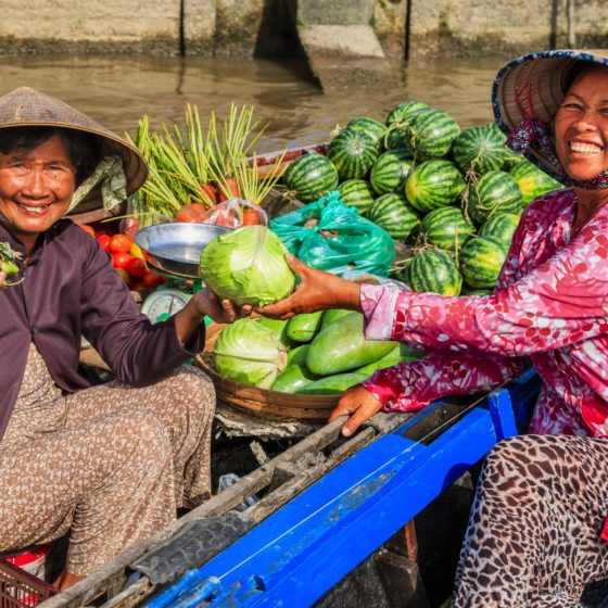 Vietnamese-woman-selling-fruits-on-floating-market-Mekong-River-Delta-Vietnam