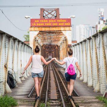 Turister går hånd i hånd på den berømte Long bien broen Hanoi