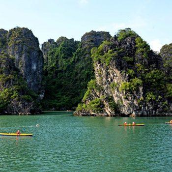 Kayaking in Halong Bay near beautiful exotic rocks