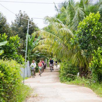Tourists biking through beautiful surroundings in mekong