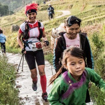 Vietnam marathon trail runners running alongside minorities in sapa rice fields