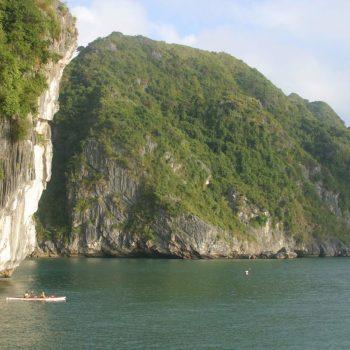 Kayaking alongside huge rock in Halong Bay